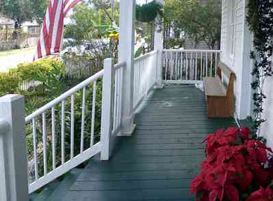 Pensacola:-Seville-Historic-District:-211-South-Florida-Blanca-Street_09.jpg:  poinsetta, deacons bench, porch, gulf coast cottage