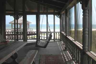 Perdido-Key:-Gothic-House_08c.jpg:  porch swing, porch, screen porch, summer house, gazebo, cedar shake roof, walkway, pier, deck, gulf of mexico, emerald water, dunes, sea oats, beach